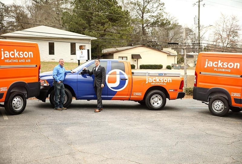 Co-owners Ben and Dale Jackson stand in front of the company's new logo and work vehicles