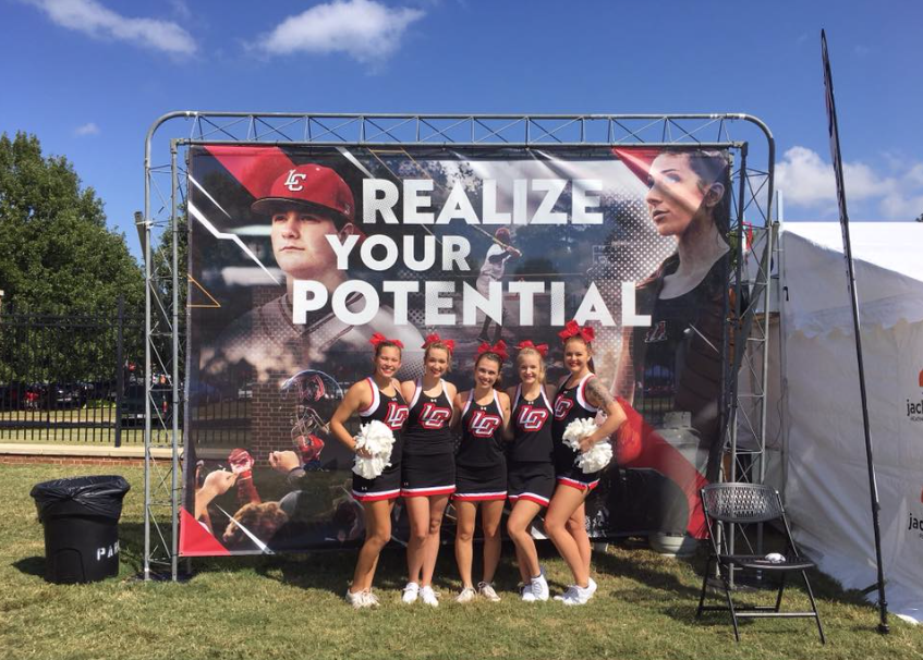 LaGrange College cheerleaders take a picture beside a Jackson Services community tent